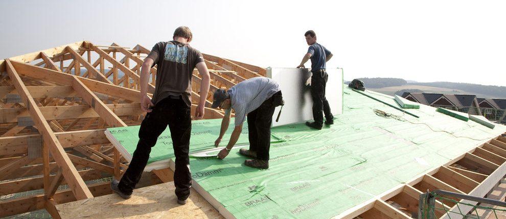 Dachhandwerker auf Dach, bringen Dachdämmung an