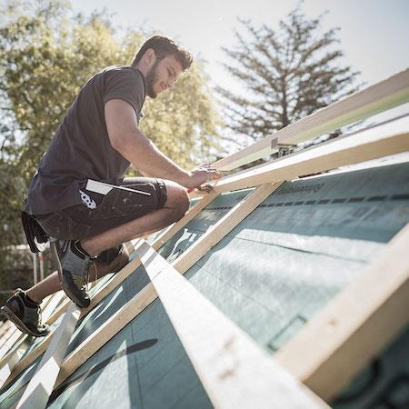Dachdecker/Zimmerer misst etwas auf dem Dach aus.