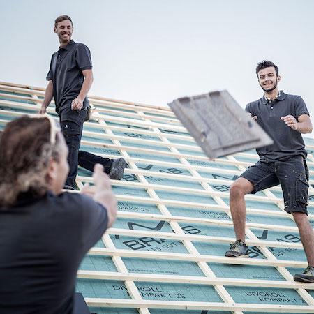 Dachdecker/Zimmerer werfen sich Dachziegel zu.