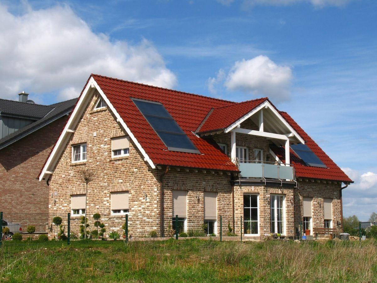 Steinhaus mit neugedecktem roten Dach und Solaranlage