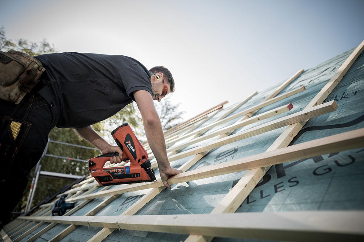 Dachdecker/Zimmerer verschraubt die Lattung auf dem Dach.
