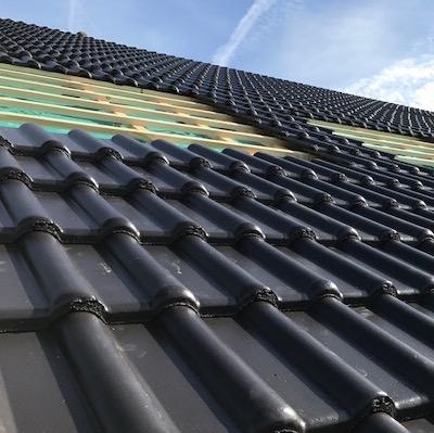 Neu gedecktes Dach mit dunklen Dachziegeln/Dachsteinen