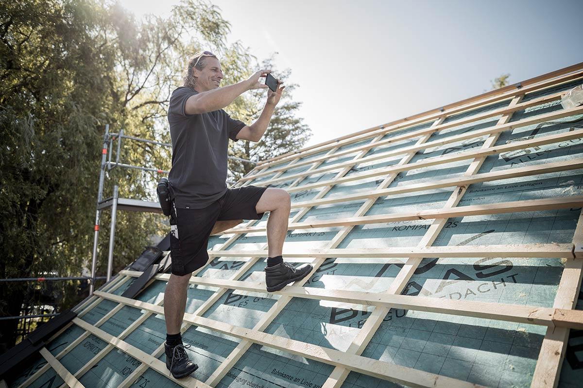 Dachdecker/Zimmerer fotografiert Fortschritt am Dach.